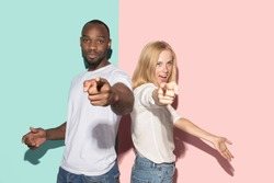 I choose you and order. The smiling mixed couple point you, want you, half length closeup portrait on studio background. The human emotions, facial expression concept. Front view. Trendy colors