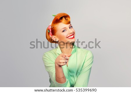 I choose you! Beautiful young businesswoman pinup retro vintage hair style pointing you while standing against white grey background