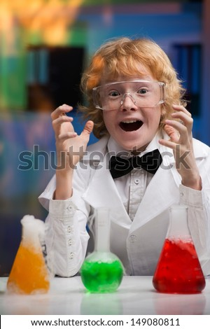 I did it! Happy little boy in lab coat gesturing while sitting at the table with laboratory equipment on it