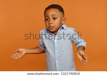 I didn't do anything wrong. Human emotions. Sad unhappy dark skinned little boy in blue shirt being at lost, shrugging shoulders, having confused clueless facial expressions, making helpless gesture