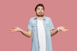 I don't know. Portrait of confused handsome bearded young man in blue casual style shirt standing with raised arms and looking at camera with answer. indoor studio shot, isolated on pink background.