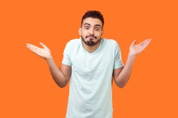 I don't know, who cares. Portrait of confused clueless brunette man with beard in white t-shirt shrugging shoulders, making no idea gesture, whatever. indoor studio shot isolated on orange background
