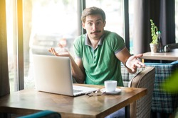 I don't know! Young confused businessman in green t-shirt sitting with laptop, looking at camera with raised arms and puzzled. business and freelancing concept. indoor shot near big window at daytime.