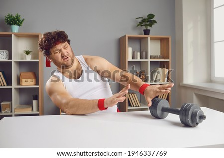 I don't want to exercise. Displeased guy pushing away fitness dumbbells. Funny lazy chubby man feeling repulsed and disgusted at sight of sports equipment unwilling to start gym training workouts Foto stock ©