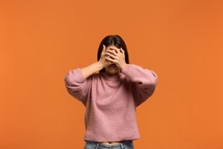 I dont want to see this. Portrait of woman in pink sweater, makes denial hand gesture, demonstrates stop sign by palm, and covers eyes with palm says no to somebody. isolated on orange wall