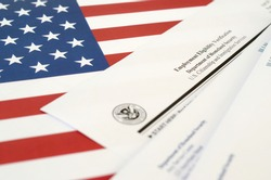 I-9 Employment Eligibility Verification blank form lies on United States flag with envelope from Department of Homeland Security