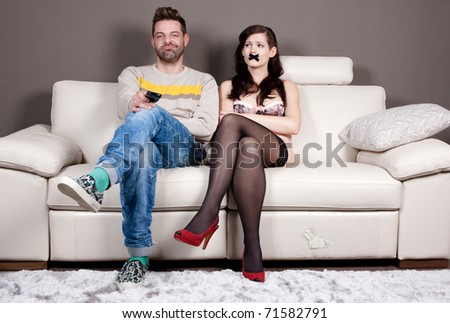 I finally managed to shut her up! Young woman with taped mouth sitting beside her boyfriend/husband who's enjoying in silence and watching TV.
