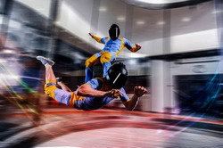 I flying. Skydiving simulation in wind tunnel. New skydiving sport in flight technology. Indoor skydiving. Training in wind tunnel. Surfing on people