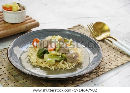 I Fu Mie or Yi Fu Mein (Mie Kering), Indonesian crispy fried noodle dish served in gravy sauce with pieces of meatball and vegetables in gray plate. Selective focus, white background Zdjęcia stock ©