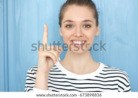 I have a great idea! Photo of energetic cute teenage smiling girl in striped t-shirt pointing her finger up in eureka sign, having great innovative thought, understanding solution she has just got.
