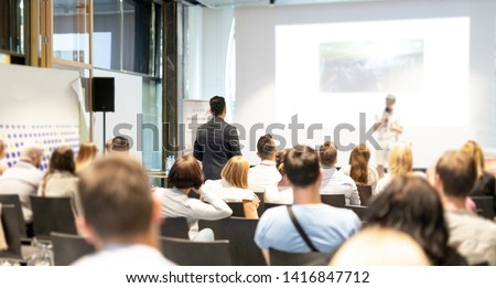 I have a question. Group of business people in conference hall. Businessman in audience standing and asking question to speeker. Conference and Presentation. Business and Entrepreneurship.