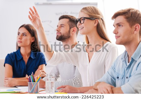 I have a question! Group of business people in smart casual wear sitting together at the table and looking away while beautiful woman raising her hand up and smiling
