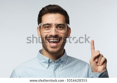 I have an idea! Handsome business man keeping finger pointed upwards, showing something above his head, making gesture with index finger. Eureka, solution sign concept