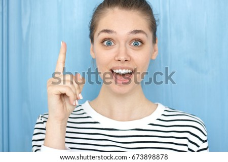 I have an idea! Pretty girl with hair bun keeping finger pointed upwards. Cute young caucasian female showing something above her head, making gesture with index finger. Eureka, solution sign concept