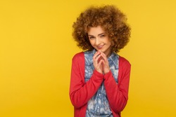 I have tricky plan! Portrait of devious cunning woman with fluffy curly hair clasping hands and smirking mysteriously, scheming cheats, evil prank. indoor studio shot isolated on yellow background