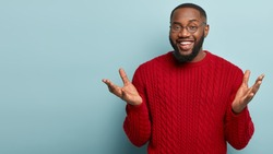 I know nothing. Horizontal shot of friendly looking black man spreads hands, gestures actively while explains something to interlocutor, stands over blue background, mock up space aside, has no idea