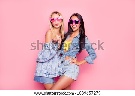 I like you! Beautiful playful cheerful women dressed in fashionable stylish shorts, shirt, jacket, top, funny star and heart glasses are embracing, sending air-kiss, isolated on bright pink background