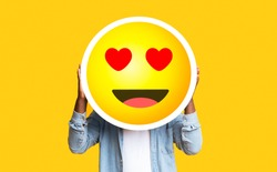 I Love Emoji. Unrecognizable Black Man Hiding Face Against Romantic Emoticon Sticker, Standing Over Yellow Background With Free Space