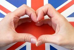 I love England. Hands make heart on United Kingdom flag background. 7 june British national day