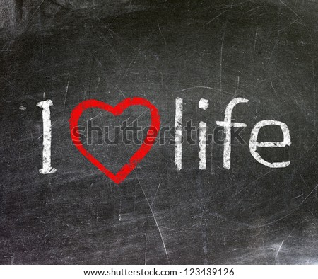 I love life handwritten with white chalk on a blackboard.