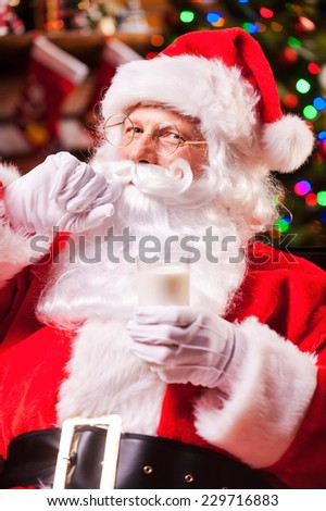 I love milk! Cheerful Santa Claus holding glass with milk and adjusting his mustache with Christmas Tree in the background
