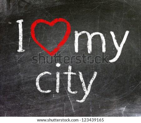 I love my city handwritten with white chalk on a blackboard.