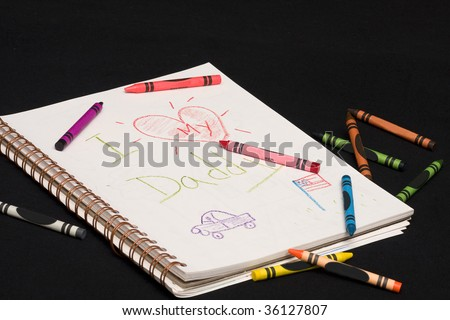 I Love My Daddy drawing by child with assorted crayons laying beside drawing pad.