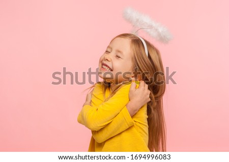 I love myself. Beautiful charming little girl with halo over head embracing herself and smiling from happiness, self-love concept, positive self-esteem. indoor studio shot isolated on pink background Foto stock ©