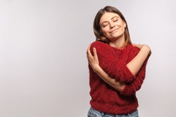 I love myself! Portrait of narcissistic selfish young woman in shaggy sweater embracing herself, closed eyes and smiling with pleasure, complacency and egoism concept.  isolated on gray background