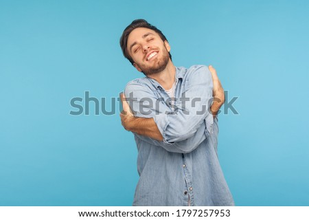 I love myself! Portrait of selfish narcissistic man in worker denim shirt embracing himself and smiling with expression of great ego, pleasure and self-esteem. studio shot isolated on blue background Foto stock ©