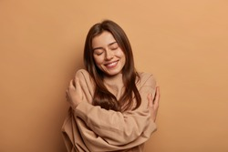 I love myself. Pretty smiling woman embraces herself gently, expresses self love, keeps eyes closed with pleasure, feels comfortable and fullfilled, being egoistic person, isolated on brown background