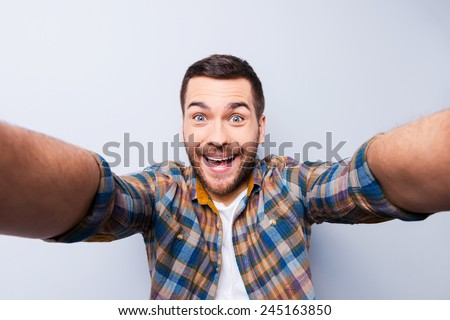 Shutterstock I love selfie! Handsome young man in shirt holding camera and making selfie and smiling while standing against grey background