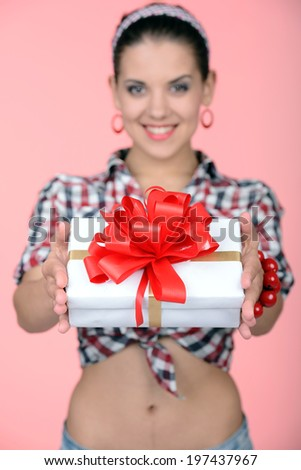 I love surprises! Happy young pin-up girl holding a present box in her left hand and standing on one leg