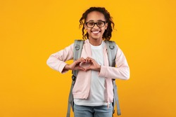 I Love To Study. Portrait of smiling African Amercian girl making heart shape with her hands and fingers near chest, pupil wearing backpack and glasses, posing on yellow studio background, copyspace