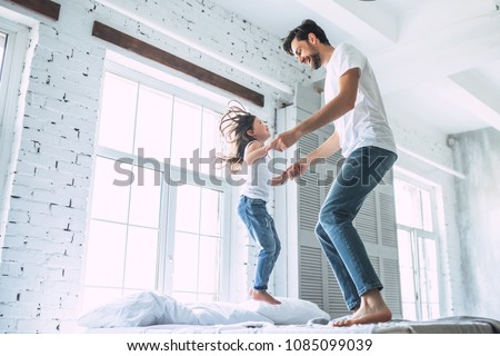 I love you, dad! Handsome young man at home with his little cute girl are having fun and jumping on bed. Happy Father's Day! #1085099039