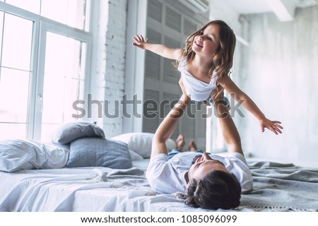 I love you, dad! Handsome young man at home with his little cute girl are having fun together. Happy Father's Day! - Shutterstock ID 1085096099