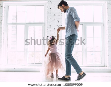 I love you, dad! Handsome young man is dancing at home with his little cute girl. Happy Father's Day! #1085099009