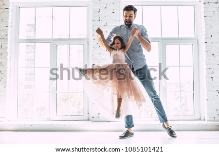I love you, dad! Handsome young man is dancing at home with his little cute girl. Happy Father's Day!