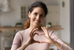 I love you. Grateful loving young latina female posing for portrait hold heart of united fingers close to breast. Happy hispanic woman look at camera show like gesture express gratitude appreciation