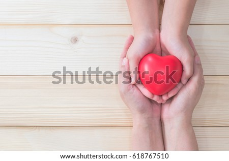 I love you Mom, Mother's Day celebration with woman parent holds young kid's hands supporting red heart gift, charity donation, nursing, parenting or children adoption family health care concept #618767510