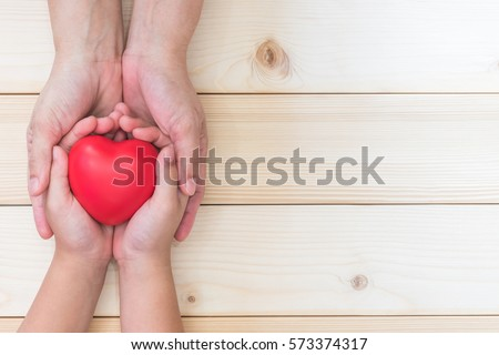 I love you Mom, Mother's woman hand holding daughter, son child kid palm supporting red heart ball, light white wood background: Nursing children home day healthcare concept: Hospital medical business #573374317