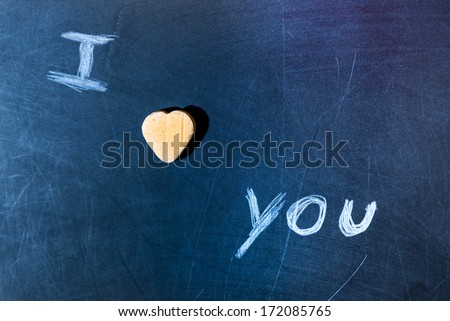 I love you on a scratched school board with candy heart
