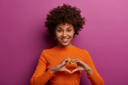 I love you with all my heart. Smiling dark skinned woman makes heart gesture, falls in love with someone, tells I am fully yours, has friendly look, dressed casually, isolated on purple background