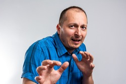 I'm afraid. Fright. Portrait of the scared man. Man with scared expression on his face making frightened gesture. Sad and scared expression face of Caucasian man in blue shirt.