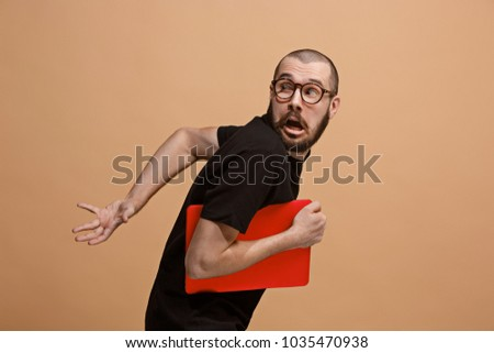 I'm afraid. Fright. Portrait of the scared man with laptop. Business man standing isolated on trendy pastel studio background. male half-length portrait. Human emotions, facial expression concept. Stock foto ©
