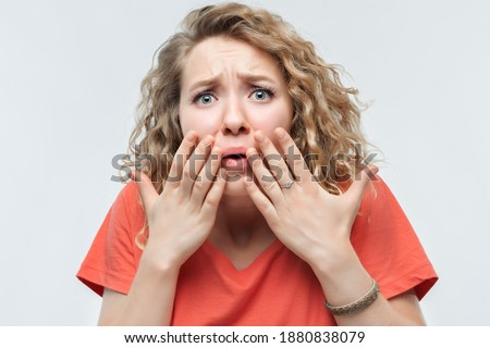 I'm afraid. Image of scared blonde girl with curly hair in casual t shirt covering her mouth with hands. Fright, phobia, panic attack, horror and facial expression concept Foto stock ©