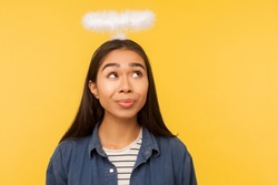 I'm angel! Portrait of thoughtful girl looking at nimbus over her head, fantasizing about paradise, heaven life, pondering question with pensive face. indoor studio shot isolated on yellow background
