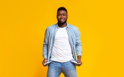I'm broke. Desperate man showing empty turned out pockets over yellow studio background