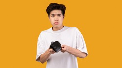 I'm Broke. Portrait of sad asian bankrupt showing his empty wallet and looking at camera. Upset crying male model standing isolated over orange studio background wall. Poverty Concept.