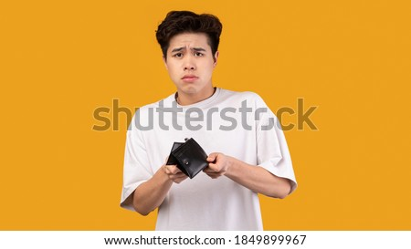 I'm Broke. Portrait of sad asian bankrupt showing his empty wallet and looking at camera. Upset crying male model standing isolated over orange studio background wall. Poverty Concept. Stock photo ©